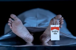 Anti smoking advertising design image. Dead body at morgue with toe tag with text Smoking kills written on it. Social awareness campaign Say NO to Tobacco and health effects of cigarette smoking.