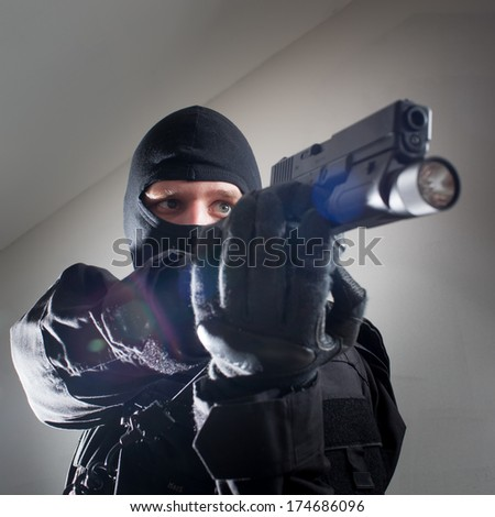 Anti terrorist unit policeman during the night strike/operation/mission in criminal's house aiming at the target (very harsh lighting is used on this shot to underline the atmosphere of night mission)