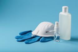 Anti-virus protection kit on a blue background, mask, rubber gloves, hand sanitizer bottles, antiseptic gel.
