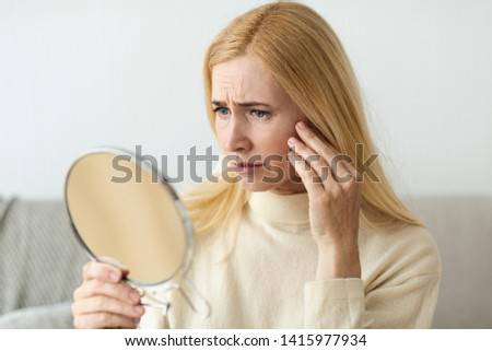 Anti-Wrinkle Skin Care. Sad Woman Looking In Mirror, Touching Her Face