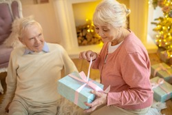 Anticipation. Elderly woman opening christmas gift from her husband and looking anticipated