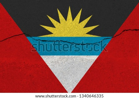 Antigua and Barbuda flag on concrete wall with crack. Patriotic grunge background. National flag of Antigua and Barbuda