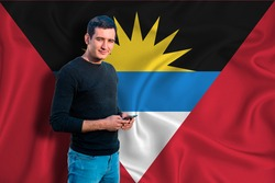 antigua and barbuda flag on the background of the texture. The young man smiles and holds a smartphone in his hand. The concept of design solutions.