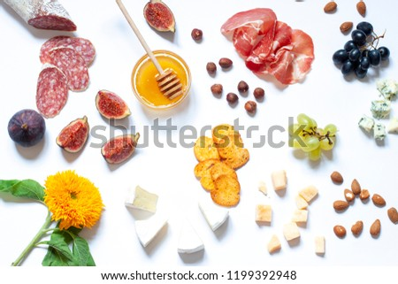 Antipasti food white flat lay with nuts, honey, cured meat, salami, cheeses, grapes and figs. Top view snack concept composition