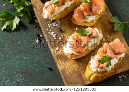 Antipasti snacks for Wine. Brushetta with Soft Cheese and Salmon on a rustic wooden board on a stone table. Copy space. Copy space.
