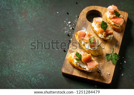 Antipasti snacks for Wine. Brushetta with Soft Cheese and Salmon on a rustic wooden board on a stone table. Copy space. Copy space. #1251284479