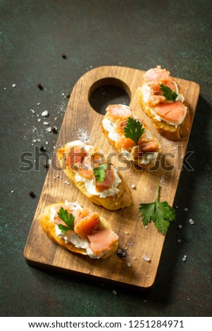 Antipasti snacks for Wine. Brushetta with Soft Cheese and Salmon on a rustic wooden board on a stone table. Copy space. Copy space. #1251284971
