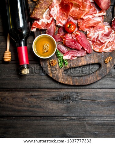Antipasto background. Different meat snacks with red wine. On a wooden background. #1337777333
