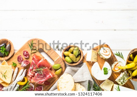 Antipasto delicatessen - sliced meat, jamon, salami, cheese, olives, ciabatta and pepperoni on white wooden table. Top view with copy space.