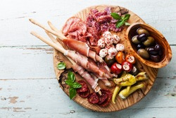 Antipasto Platter Cold meat plate with grissini bread sticks on wooden background