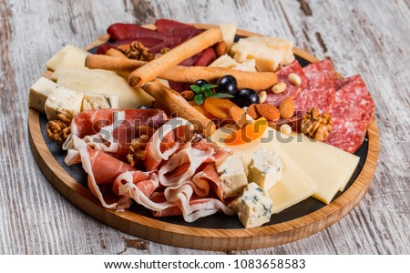 Antipasto platter cold meat with grissini bread sticks, prosciutto, slices ham, beef jerky, salami and cheese platter on wooden board over rustic background. Appetizer, catering food concept