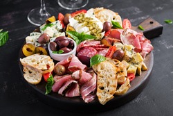 Antipasto platter with ham, prosciutto, salami, blue cheese, mozzarella with pesto and olives on a wooden background.