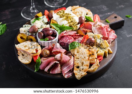 Antipasto platter with ham, prosciutto, salami, blue cheese, mozzarella with pesto and olives on a wooden background. Foto stock ©