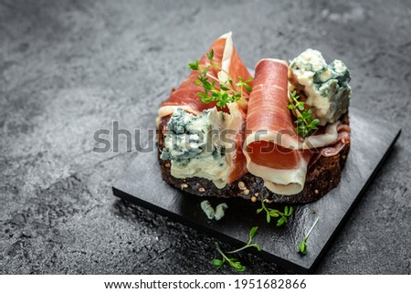 Antipasto platter with jamon, prosciutto, blue cheese, Appetizers. meat snacks for red wine. Appetizer on a slate board. ストックフォト ©