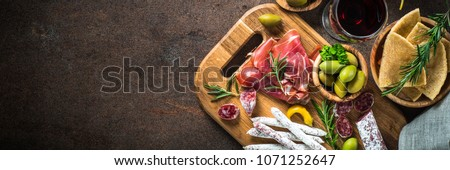 Antipasto - sliced meat, ham, salami, olives and glass wine on dark stone table. Top view long banner format.