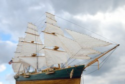 Antiquarian wooden scale model of the clipper tall ship, close-up. Dramatic sky in the background. Traditional craft, souvenirs, hobby, collecting, vintage, modeling. Zero waste concept