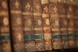 Antique aged books on wooden shelf. Old books background. Shallow depth of field