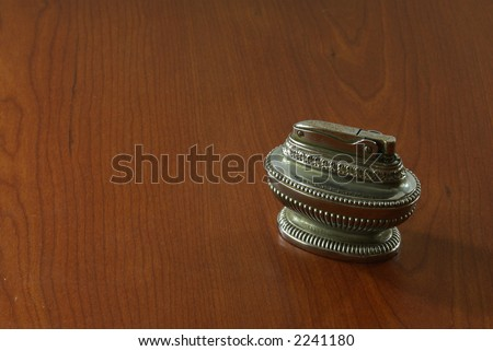 Antique aged silver butane table cigarette lighter on wooden background.