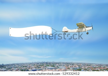 Antique Airplane with advertise board fly on Cityscape bird eye view with blue sky, Bangkok Thailand.