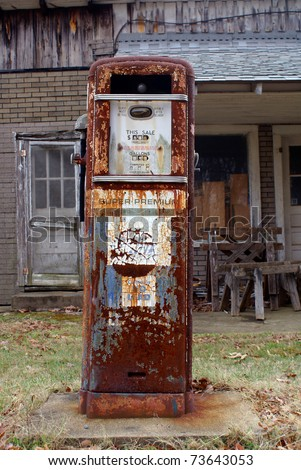 Antique American gas pump. Rusted and with chipped off paint in front of a old brick building. Logos & brand names are removed.