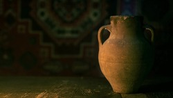 Antique Ancient Old Historically Items on Table. Vintage photo.  Tools of ancient peoples. Old Retro Ancient Historical Jug in old table footage. An ancient Armenian carpet hangs on the back wall.