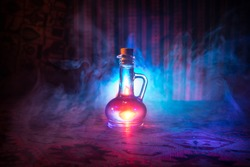 Antique and vintage glass bottle on dark foggy background with light. Poison or magic liquid concept.