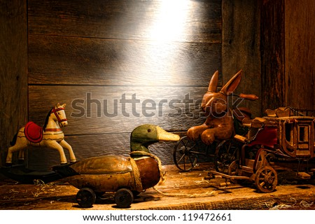 Antique and vintage wood toys reproductions with wooden pull duck toy on wheels in an old house attic