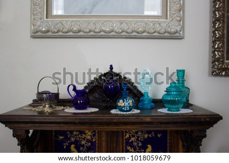 Antique antique tableware and bottles of female perfume from the 18th-19th century on an antique antique chest of drawers. #1018059679