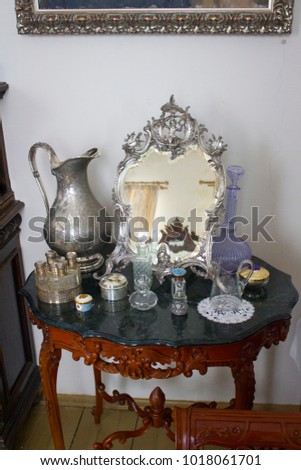 Antique antique ware, a vintage bottle of women's perfume, things of the 18th-19th century, items for women on an antique table in the interior. #1018061701