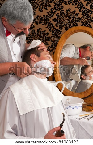 Antique barber shaving a customer the old-fashioned way