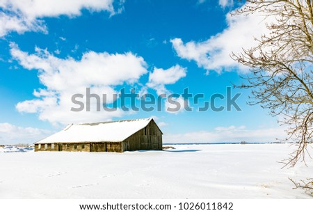Antique barn in rural Quebec Canada in mid winter in a snow scene.