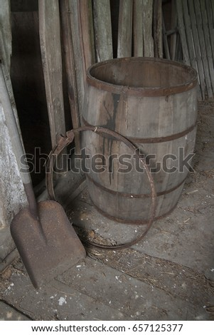 Antique barrel and shovel abandoned in an old wooden barn. #657125377