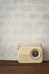 Antique beige color radio on the wooden shelves decoration and brick wall interior classic home and living retro building. Vintage coffee shop decoration with copy space on background.