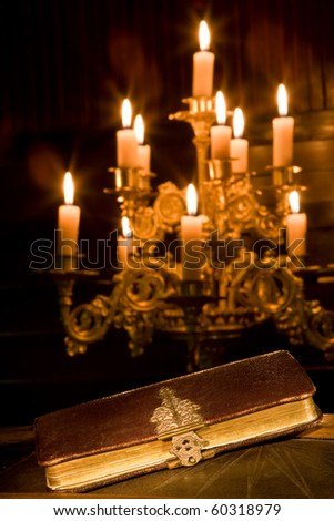 Antique bible in a chapel with candles - stock photo