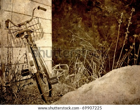Antique bicycle leaning against a building in the winter, grunge textured.