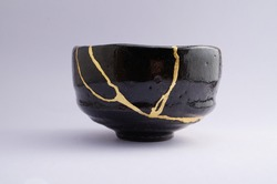 Antique black and gold Kintsugi bowl. Gold cracks restoration on old Japanese pottery restored with the antique restoration technique.The unique beauty of imperfections.