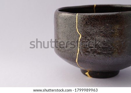 Antique black and gold Kintsugi bowl. Gold cracks restoration on old Japanese pottery restored with the antique restoration technique.The unique beauty of imperfections.  Сток-фото ©