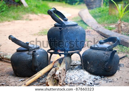 Antique black kettles or coffeepot on an open fire