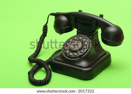 Antique black landline phone on green backdrop