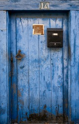 antique blue door faded by time, with a black mailbox and an ochre handle, label with number 14