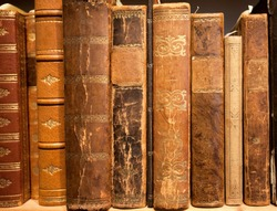 Antique books in leather covers, printed at 19th century and before. Knowledge background of library or bookstore.