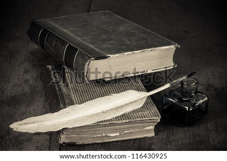 Antique books, quill and inkwell on the grunge table background