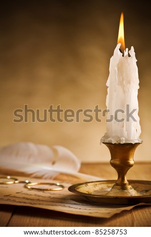 Antique brass candlestick with burning candle - stock photo