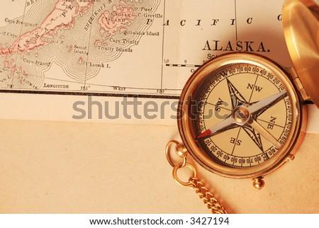 antique brass compass over old alaska map 3427194