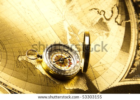 Antique brass compass over old map - stock photo
