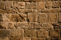 Antique brick wall in sunligh. Cracked and scratched on brown masonry or brickwork. Close up shot. Abstract background or texture.