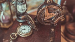 Antique bronze compass and retro adventure accessories in vintage style image.