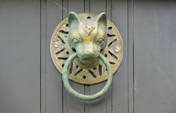 Antique bronze door knocker in the shape of a cat's head