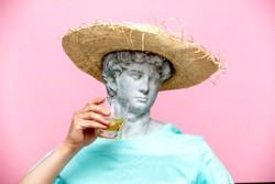 Antique bust of male in hat with whiskey glass on pink background. Ready for summer vacation