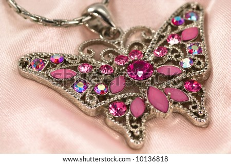 Antique butterfly necklace on pink silk #10136818